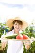 畑で採れた野菜を差し出す女性