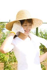 畑仕事中に汗を拭く女性