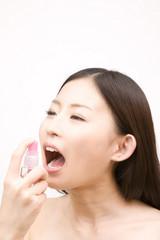 口臭スプレーを使う女性