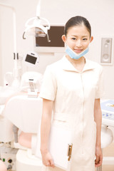 治療台の前に立ち微笑む歯科衛生士