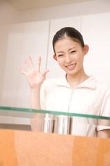 受付に立ち手を振る歯科衛生士