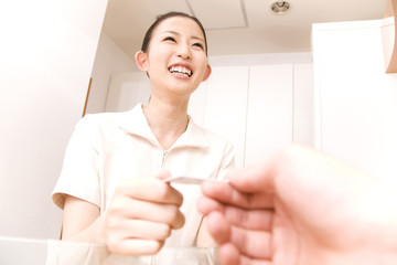 男性患者から保険証を受け取る歯科衛生士