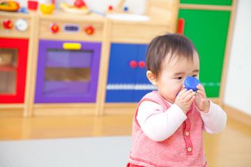 おもちゃで遊ぶ乳児