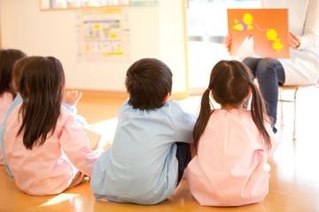 紙芝居を見る幼稚園児の後姿