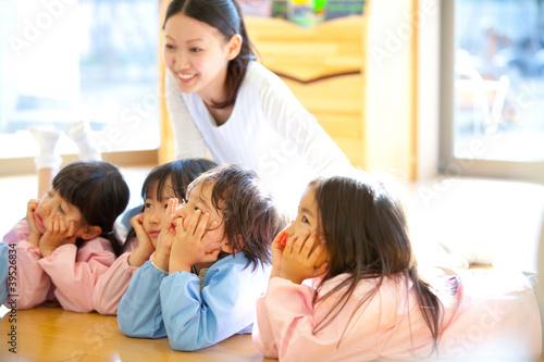 頬杖をついて微笑む幼稚園児と笑顔の幼稚園教諭