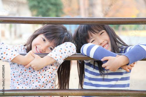遊具につかまって微笑む女の子2人