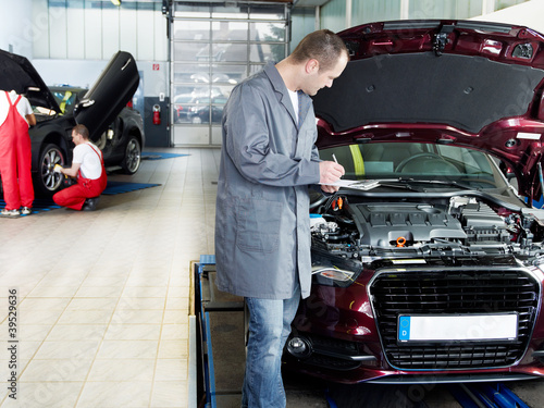 Master mechanic checking the engine bay, workers in background