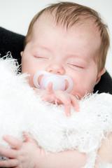 Newborn sleeping child on white blanket