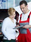 Motor mechanic explaining repair costs to female customer