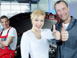 Mechanic and woman in front of car and worker show thumb up