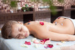 .Glad woman receiving a massage with hot stone in a spa center