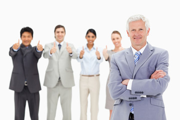 Close-up of a multicultural business team with their thumbs-up with a mature man crossing his arms