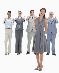 Laughing woman with a business team with their thumbs-up