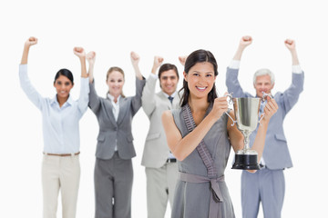 Close-up of a woman holding a cup with a business team raising their arms