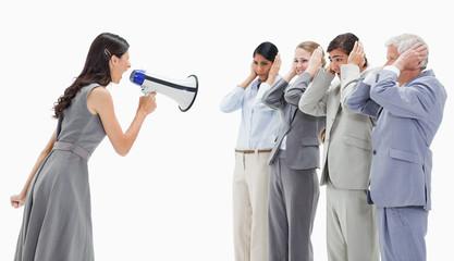 Woman yelling in a megaphone at business people