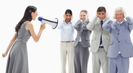 Woman yelling in a megaphone at business people with their hands over their ears