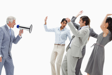 Man yelling in a megaphone at business people