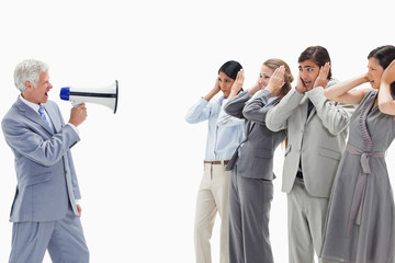 Man yelling in a megaphone at business people with their hands over their ears