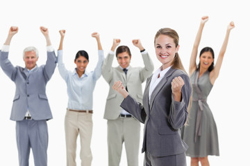 Blonde woman with business people raising their arms behind her