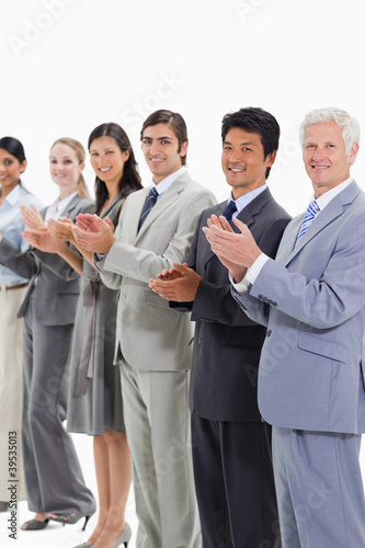 Multicultural smiling business people applauding and posing