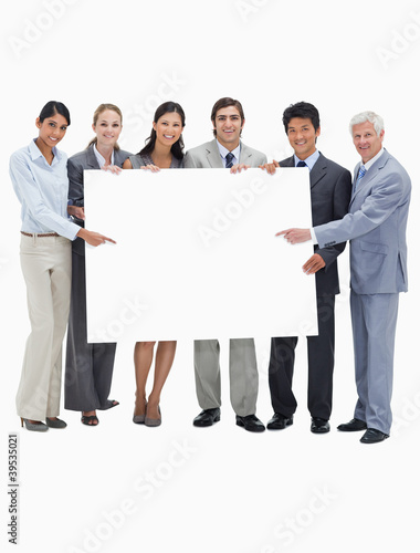 Smiling multicultural business team holding and showing a placard