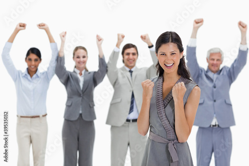 Close-up of a smiling woman clenching her fists with a business team raising their arms