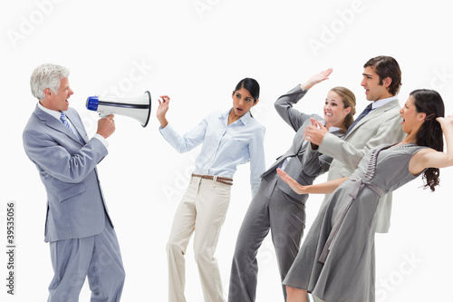 Man yelling in a megaphone at stunned business people