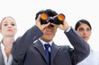 Businessman looking up through binoculars with two girls behind him