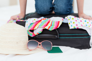 Woman, trying hard to pack for a sun holiday