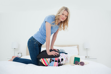 Angry looking woman trying to close her suitcase by pushing on it while on the bed
