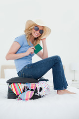 Smiling woman sitting on her suitcase on the bed while holding her passport