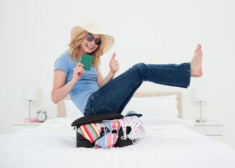 Woman laughing as she balances on the suitcase giving a thumbs up