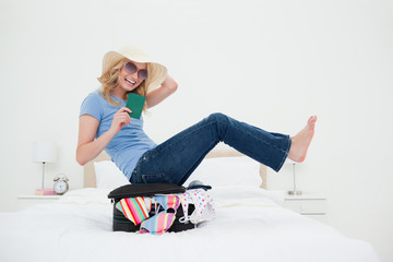 Woman laughing as she balances on her suitcase, with hat and glasses on