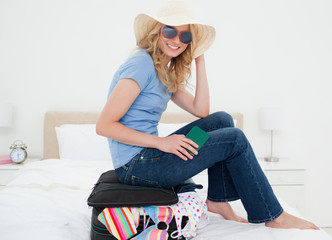 Woman sitting on her suitcase, smiling with hat and glasses on