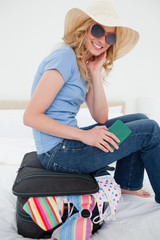 Close up, woman sitting on a suitcase while smiling and wearing a hat and glasses