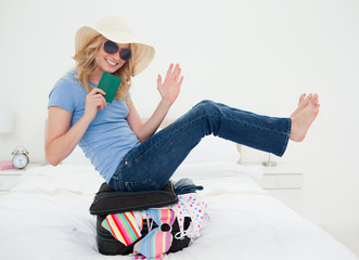 Balancing woman smiles and waves on top of her suitcase