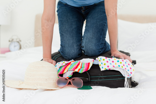 Woman trying to pack her suitcase on the bed, for a holiday