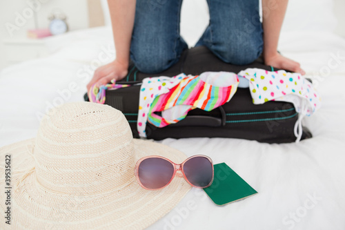 Woman kneeling on suitcase in an attempt to make things fit