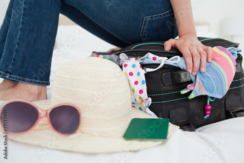 Woman trying to close her suitcase by sitting on it, focus on the suitcase