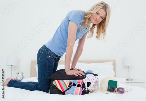 Woman looking annoyed as her suitcase will not close