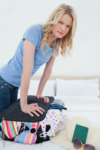 Close up, annoyed woman trying to close her suitcase on the bed