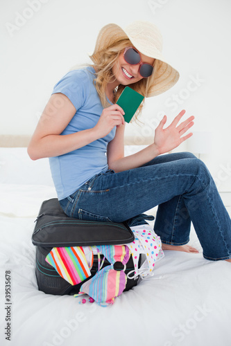Pleased woman waving as she sits on her suitcase with passport in hand