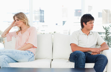 Man and woman sitting at opposite ends of then couch, both looking upset