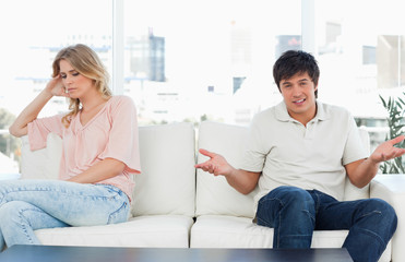 Man looking confused as the woman sits away from him looking upset