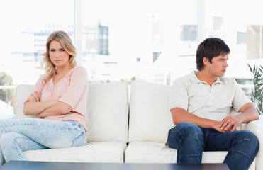 Woman facing forward and annoyed with crossed arms, while the man looks angry