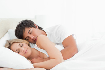 Man and woman sleeping in bed together while holding each other