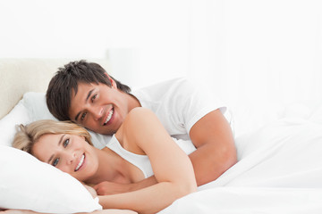 Man and woman lying in bed close to each other as they smile looking forward