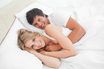 Man and woman in bed holding each other looking up and smiling
