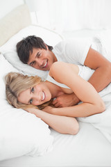 Close up, man and woman in bed smiling as they look up