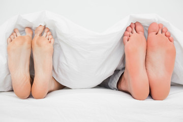 Two pairs of feet, in bed beside each other pointing straight up